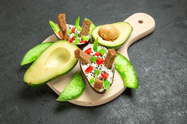 Vista frontal de abacates cremosos com pão e pimenta e abacates frescos no espaço cinza