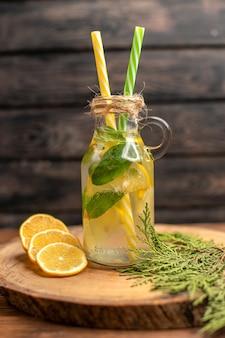 Vista frontal de água desintoxicante fresca em um copo servido com tubos e limas de limão em uma bandeja marrom