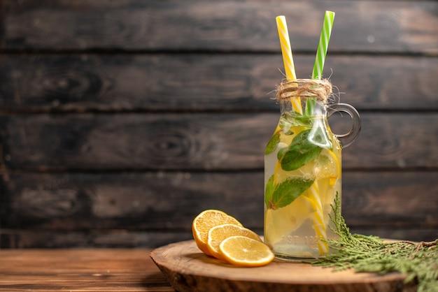 Vista frontal de água desintoxicante fresca em um copo servido com tubos e limas de limão
