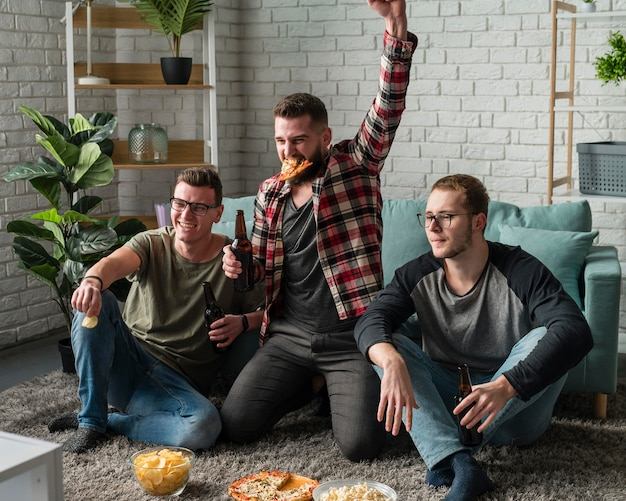 Vista frontal de alegres amigos do sexo masculino assistindo esportes na tv e comendo pizza