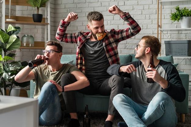 Vista frontal de alegres amigos do sexo masculino comendo pizza e assistindo esportes na tv