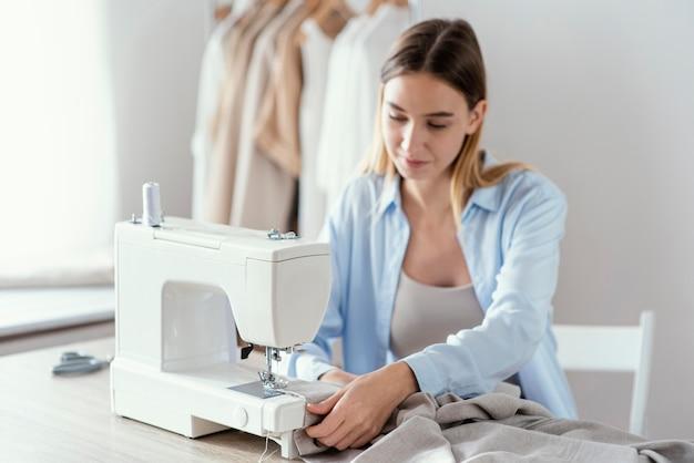 Vista frontal de alfaiate feminina usando máquina de costura no estúdio
