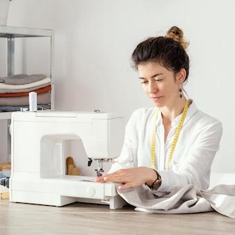 Vista frontal de alfaiate trabalhando com máquina de costura