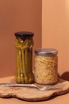 Vista frontal de alimentos em conserva em potes com garfo