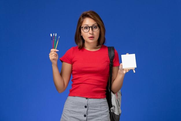 Vista frontal de aluna de camisa vermelha com mochila segurando borlas para desenhar na parede azul-clara