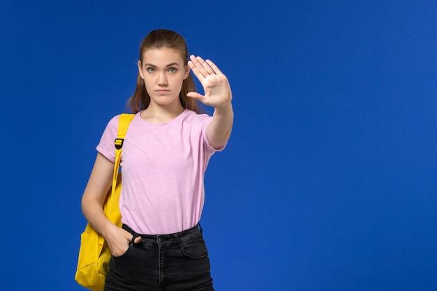 Vista frontal de aluna em camiseta rosa com mochila amarela na parede azul