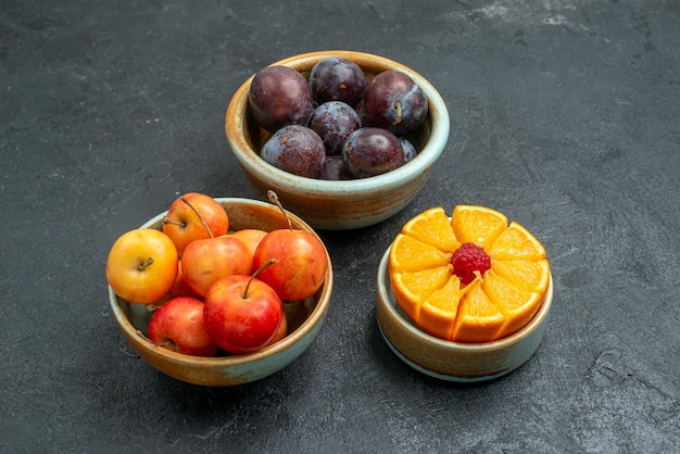 Vista frontal de ameixas frescas com cerejas em fundo escuro frutas maduras frescas