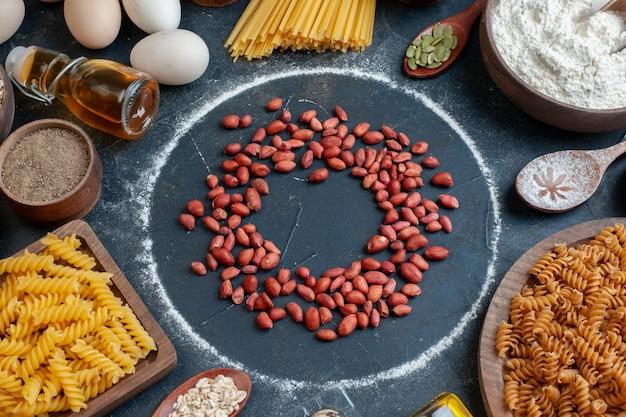 Vista frontal de amendoim vermelho fresco com temperos de massa crua e ovos no escuro