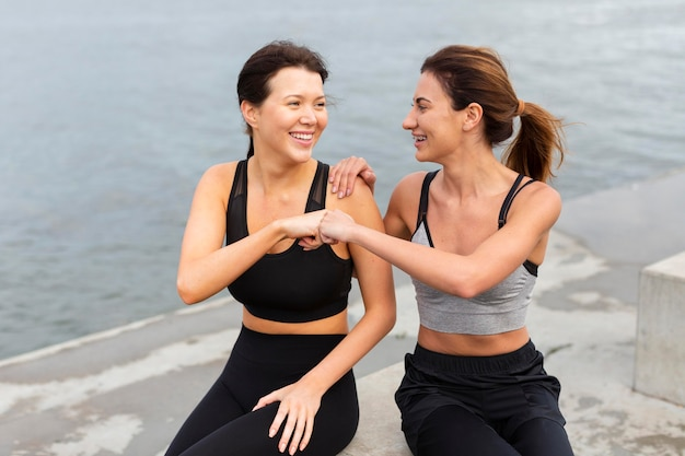 Vista frontal de amigas se divertindo enquanto se exercitam juntas ao ar livre
