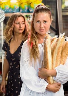 Vista frontal de amigas segurando baguetes de pão