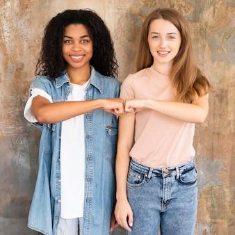 Vista frontal de amigas sorridentes batendo os punhos