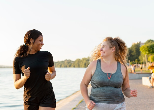 Vista frontal de amigas sorridentes correndo juntas