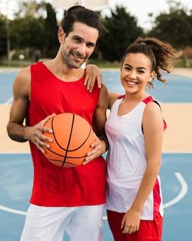 Vista frontal de amigos com bola de basquete