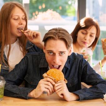 Vista frontal de amigos comendo hambúrgueres