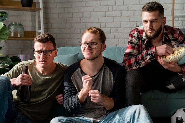 Vista frontal de amigos do sexo masculino assistindo esportes na tv e tomando cerveja e lanches