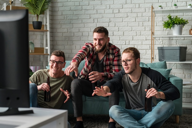 Vista frontal de amigos do sexo masculino assistindo esportes na tv juntos