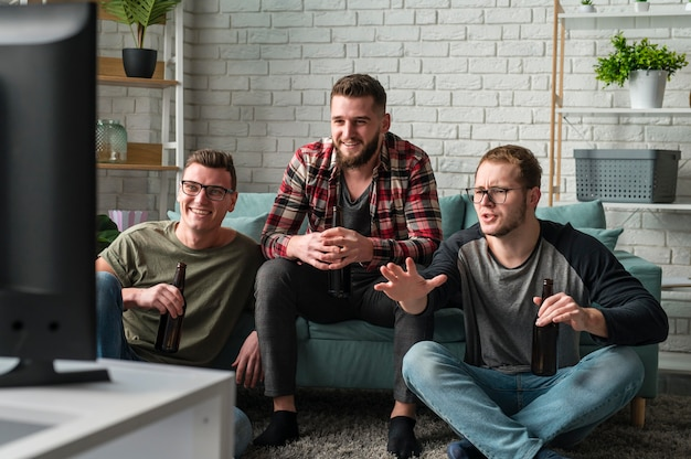 Vista frontal de amigos do sexo masculino assistindo esportes na tv