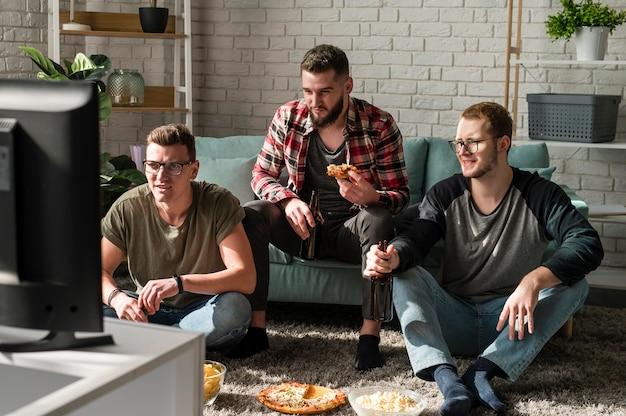 Vista frontal de amigos do sexo masculino comendo pizza com cerveja e assistindo esportes na tv
