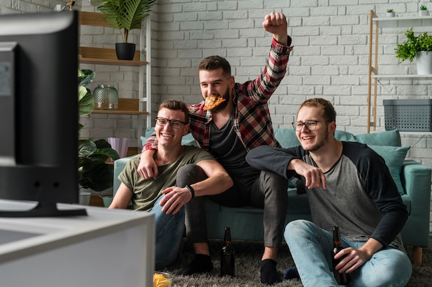 Vista frontal de amigos do sexo masculino comendo pizza e assistindo esportes na tv
