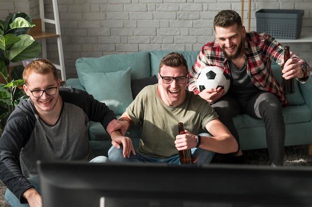 Vista frontal de amigos do sexo masculino fervorosos assistindo esportes na tv com futebol