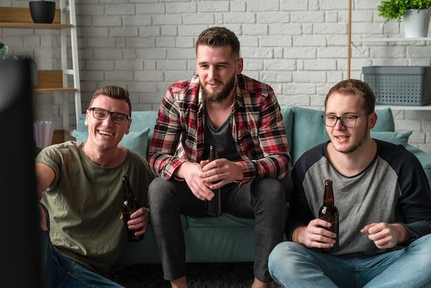 Vista frontal de amigos do sexo masculino sorridentes assistindo esportes na tv