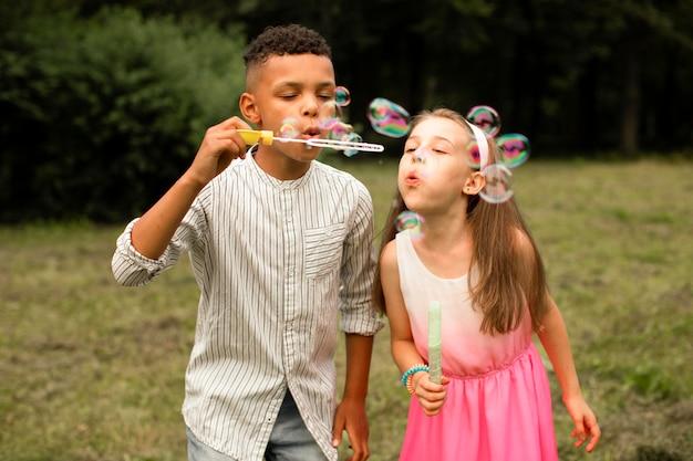 Vista frontal de amigos fazendo bolhas de sabão