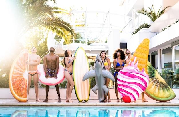Vista frontal de amigos na festa na piscina com colchão inflável lilo e roupa de banho