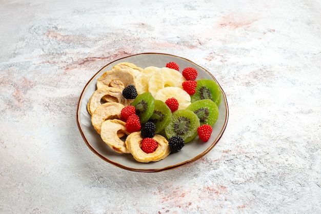 Vista frontal de anéis de abacaxi secos com confitures de kiwis secos e maçãs na superfície branca