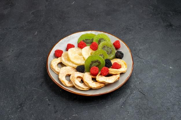 Vista frontal de anéis de abacaxi secos com kiwis secos e maçãs na superfície cinza escuro frutas passas secas doces açúcar doce