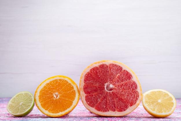 Vista frontal de anéis de citrinos toranjas laranjas limas na mesa de luz