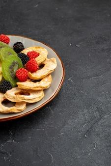 Vista frontal de anéis secos de abacaxi com kiwis secos e maçãs na superfície cinza escuro frutas secas doces e doces
