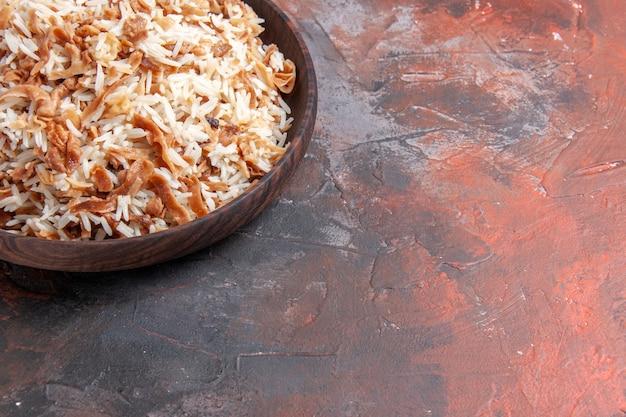 Vista frontal de arroz cozido com fatias de massa na superfície escura foto prato refeição comida escura