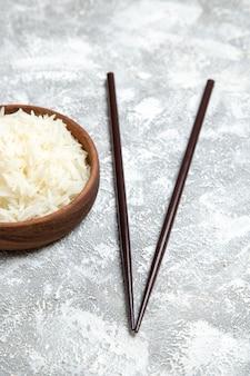 Vista frontal de arroz cozido delicioso dentro de um prato marrom no chão branco farinha de arroz cozinhando o prato de jantar