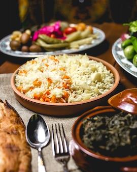 Vista frontal de arroz cozido em um prato com batatas cozidas e abóbora
