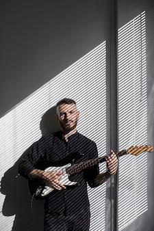 Vista frontal de artista masculino tocando guitarra elétrica ao lado da janela