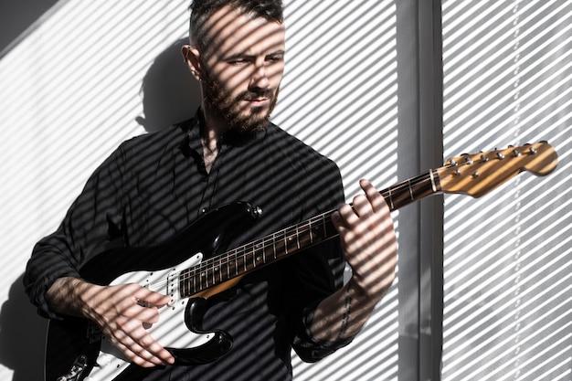 Vista frontal de artista masculino tocando guitarra elétrica com as sombras das cortinas