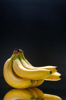 Vista frontal de bananas frescas amarelas em uma parede negra de frutas tropicais com cores exóticas