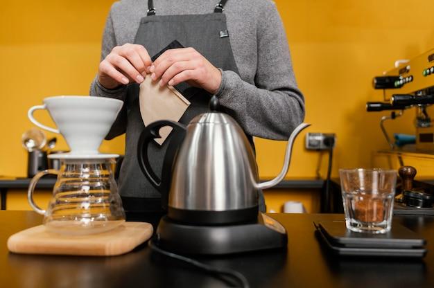 Vista frontal de barista masculino com avental fazendo café