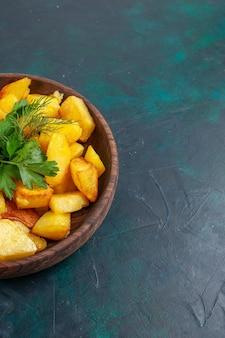 Vista frontal de batata cozida fatiada refeição deliciosa com verduras dentro de um prato marrom na superfície azul escura