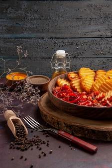 Vista frontal de batatas assadas com legumes cozidos e temperos em espaço escuro