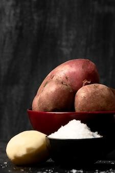 Vista frontal de batatas em uma tigela com sal
