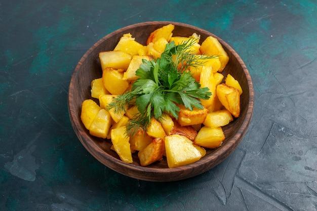Vista frontal de batatas fatiadas cozidas com verduras dentro de um prato marrom na superfície azul escura
