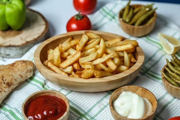 Vista frontal de batatas fritas com ketchup e maionese de tomate e pimentão na mesa