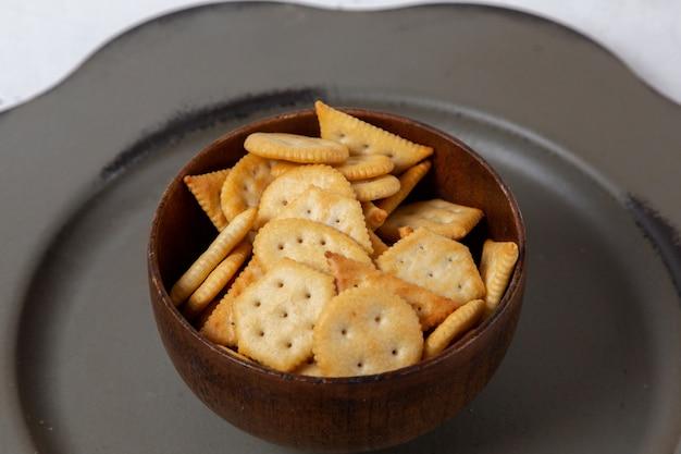 Vista frontal de batatas fritas e biscoitos dentro da placa marrom redonda dentro da placa cinza