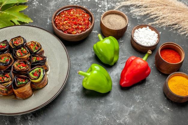 Vista frontal de berinjela recheada rola especiarias em pequenas tigelas sal pimenta pimenta vermelha açafrão adjika pimentas em fundo cinza
