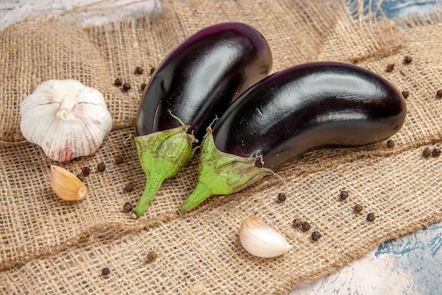 Vista frontal de berinjelas com alho pimenta preta em toalha de mesa de palha