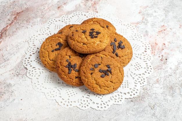 Vista frontal de biscoitos de areia deliciosos, doces perfeitos para uma xícara de chá na superfície branca