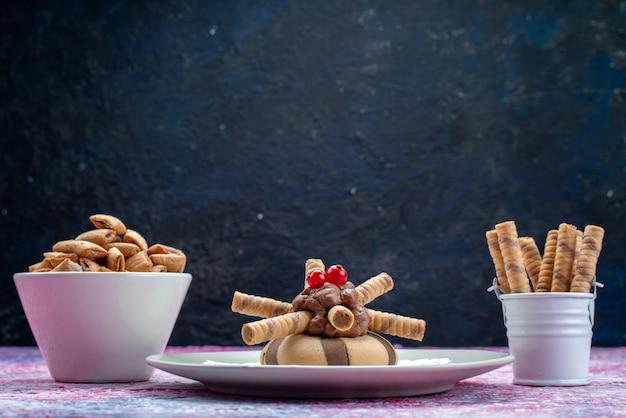 Vista frontal de biscoitos de chocolate junto com batatas fritas na superfície escura