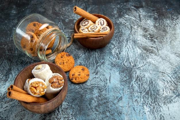 Vista frontal de biscoitos doces com confitures na superfície escura