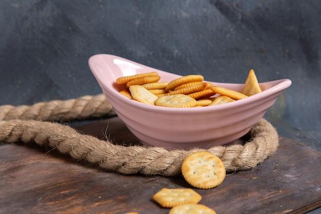 Vista frontal de biscoitos e bolachas no interior do prato rosa com cordas na mesa de madeira